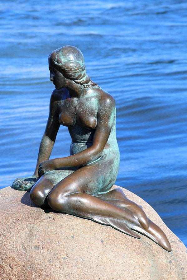 The Little Mermaid Statue is displayed on a rock by the waterside at the Langelinie promenade in Copenhagen, Denmark