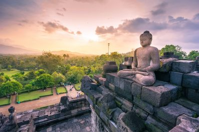 Carved stone buddha statue in small stupa around top of Borobudur, world largest buddhist temple in Yogyakarta, Indonesia